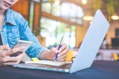Kobiety ręka pisze na notepad z piórem i używa komórkę p zdjęcia royalty free