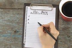 Kobiety ręka pisze nowego roku ` s postanowieniach Nowego Roku ` s postanowienie zdjęcia stock