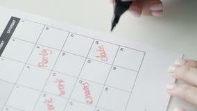 Kobiety ręka pisze z czerwieni filc piórem na kalendarzowej słowo dacie zdjęcie wideo