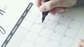 Kobiety ręka pisze z czerwieni filc piórem na kalendarzowym słowa przyjęciu zbiory