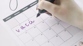 Kobiety ręka pisze z fiołek filc piórem na kalendarzowym słowo wakacje zbiory
