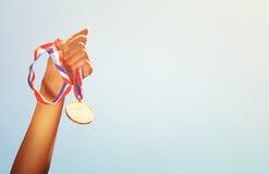 Kobiety ręka podnosząca, trzymający złotego medal przeciw niebu nagrody i zwycięstwa pojęcie Obrazy Stock