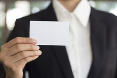 Kobiety ręka pokazuje wizytówkę - zbliżenie strzał na blured z powrotem obrazy stock