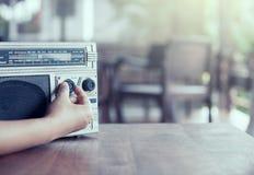 Kobiety ręka przystosowywa rozsądną pojemność na retro radiowej kasecie Obrazy Stock