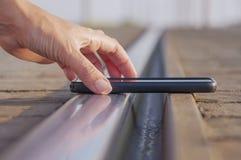 Kobiety ręka stawia smartphone na linii kolejowej obraz royalty free