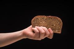Kobiety ręka trzyma świeżego i smakowitego brown chleb Fotografia Stock