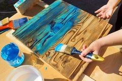 Kobiety ręka trzyma akrylowego muśnięcie, maluje drewnianego biurko z błękitnym kolorem w ogródzie Lato czas, odświeżanie Leworęc Zdjęcie Royalty Free