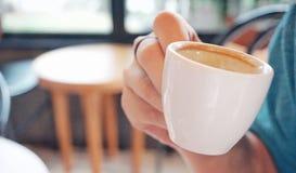 kobiety ręka trzyma białą filiżankę gorąca kawa Zdjęcie Stock