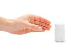 Kobiety ręka trzyma białą medycyny butelkę Fotografia Stock