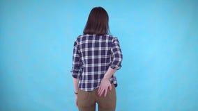 Kobiety ręka trzyma jej dno ponieważ jest ból powodować hemoroidem na błękitnym tle zbiory