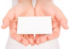 Kobiety ręka trzyma pustego papieru wizytówkę odizolowywająca na białym b zdjęcie stock