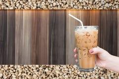 Kobiety ręka trzyma szklaną lukrową kawę na drewnianym i surowym kawowych fasoli tle Zdjęcia Stock