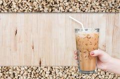 Kobiety ręka trzyma szklaną lukrową kawę na drewnianym i surowym kawowych fasoli tle Zdjęcia Royalty Free