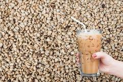 kobiety ręka trzyma szklaną lukrową kawę na unroasted kawowym surowym fasoli tle Fotografia Stock