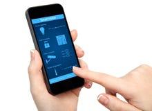 Kobiety ręka trzyma telefon z systemu mądrze domem zdjęcia royalty free