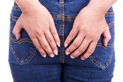 Kobiety ręka trzyma zadek: Pojęcie hemoroidy obraz stock