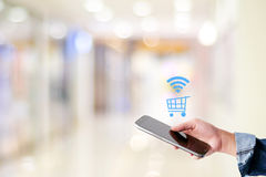 Kobiety ręka używać mądrze telefon i robiący zakupy ikonę nad plama sklepem w Obrazy Royalty Free