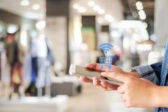 Kobiety ręka używać mądrze telefon i robiący zakupy ikonę nad plama sklepem w Zdjęcie Royalty Free