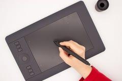 Kobiety ręka w czerwonym rękawie rysuje stylus na grafiki pastylce obraz stock
