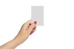 Kobiety ręka z czerwonego gwoździa chwyta wizytówki pustym egzaminem próbnym up Zdjęcia Royalty Free