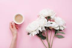 Kobiety ręka z filiżanką kawy i piękną białą peonią kwitnie na różowym pastelowym stołowym odgórnym widoku Wygodny śniadanie w mi obrazy stock