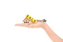 Kobiety ręka z słowa sprzedażą i dom z kluczami Obraz Stock