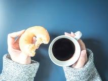 Kobiety ręka z sukiennym chwytem czarna kawa w białej filiżance i je Zdjęcie Royalty Free