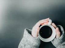 Kobiety ręka z sukiennym chwytem czarna kawa w białej filiżance na morn Obraz Stock