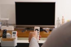Kobiety ręki chwyt pilot do tv TV pudełko w żywym pokoju czarny ekran TV Obrazy Royalty Free
