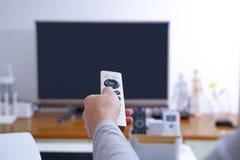 Kobiety ręki chwyt pilot do tv TV pudełko w żywym pokoju, czerń parawanowy TV Fotografia Royalty Free