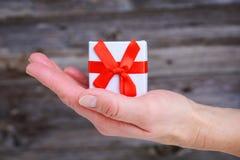 Kobiety ręki chwyta prezenta mały pudełko Zdjęcie Royalty Free