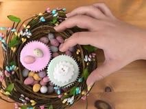 Kobiety ręki dojechanie dla Wielkanocnej babeczki obrazy stock