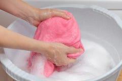 Kobiety ręki domycie dział woolen pralnię w popielatym plastikowym basenie Udział mydlany biały detergent Sucha skóra i drażnieni obraz stock