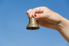 Kobiety ręki gwoździ chwyta żelaza czerwony dzwon na niebieskim niebie Obrazy Royalty Free