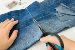Kobiety ręki holdig nożyce i tnący za fałdowym w przyrodnich niebieskich dżinsach z wielką dziurą dalej dyszy nogę Robić drelichó zdjęcia stock