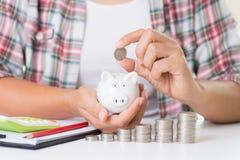 Kobiety ręki kładzenia pieniądze moneta na stercie monety i inny wręczamy mieniu czerwonego ołówek i używać kalkulator banka pien zdjęcia stock