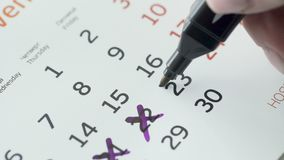 Kobiety ręki krzyża 23st dzień miesiąc na papieru kalendarzu zbiory