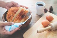 Kobiety ręki mienia bochenek domowej roboty chleb z sezamem na drewno stołu tle z jajkami i kawą Zdjęcia Royalty Free