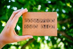 Kobiety ręki mienia kartonu karta z słowami Declutter Twój życie Zdjęcia Stock