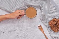 Kobiety ręki mienia mleka herbata z słodkiej czekolady ciastkiem Fotografia Stock