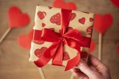 Kobiety ręki mienia prezenta pudełko z czerwonym łękiem Wiele serca na drewnianym tle w defocus Walentynki ` s dnia pojęcie fotografia stock