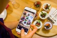 Kobiety ręki mienia telefon bierze fotografię smakowite babeczki z jagodami Instagram fotografii blogging i cukierki pojęcie obraz royalty free