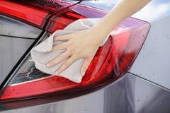 Kobiety ręki obcierania samochodu sucha powierzchnia z microfiber płótnem po wa Zdjęcie Stock
