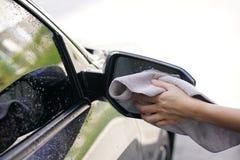 Kobiety ręki obcierania samochodu sucha powierzchnia z microfiber płótnem po wa Obraz Stock