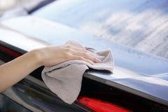 Kobiety ręki obcierania samochodu sucha powierzchnia z microfiber płótnem po wa Zdjęcia Royalty Free