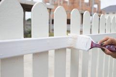 Kobiety ręki pracownik maluje bielu ogrodzenie Zdjęcia Stock