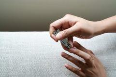 Kobiety ręki rozcięcie przybija używać gwoździa cążki na kanapie przy żywym pokojem zdjęcie stock
