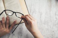Kobiety ręki szkła i książka zdjęcie stock