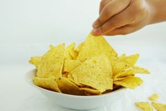 Kobiety ręki zrywania kukurydzani nachos lub tortilla układy scaleni od białego pucharu Obraz Stock