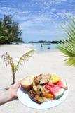 Kobiety ręka niesie tradycyjnego tropikalnego jedzenie w Muri lagunie Raroto Zdjęcie Royalty Free